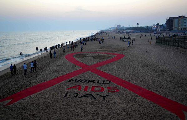 印度沙雕艺术家Sudarsan Pattnaik在普瑞海滩塑造了世界上最长的红丝带标志。(ASIT KUMAR/AFP/Getty Images)