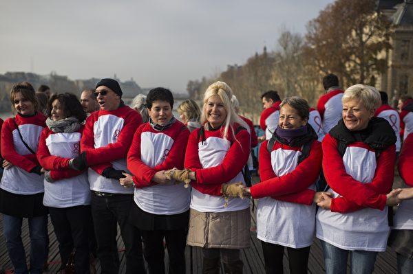 11月30日,人们参加在巴黎举行的世界爱滋病日的集会,以双手交织成象征物红丝带的形状。(MARTIN BUREAU/AFP/Getty Images)
