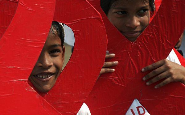 11月30日,世界爱滋病日前夕,印度加尔各答孩童和社会工作者举办活动,期待唤起人们对爱滋病传播的认知。(DIBYANGSHU SARKAR/AFP/Getty Images)