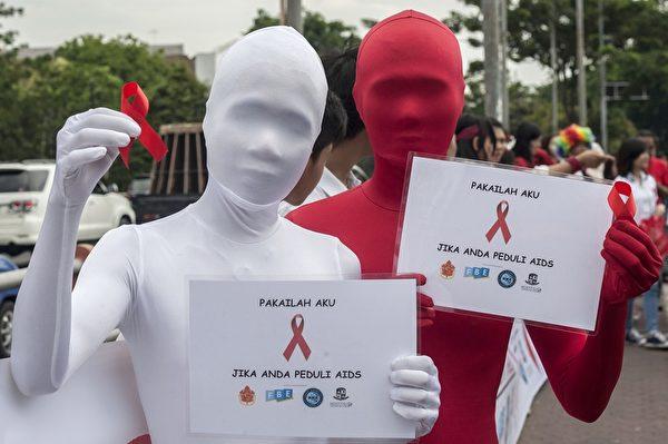 12月1日,在印尼泗水,两个活动者展示爱滋病的象征物红丝带。根据一项研究,2013年印尼有AIDS发病者45,000例,14,400例因而死亡。(JUNI KRISWANTO/AFP/Getty Images)