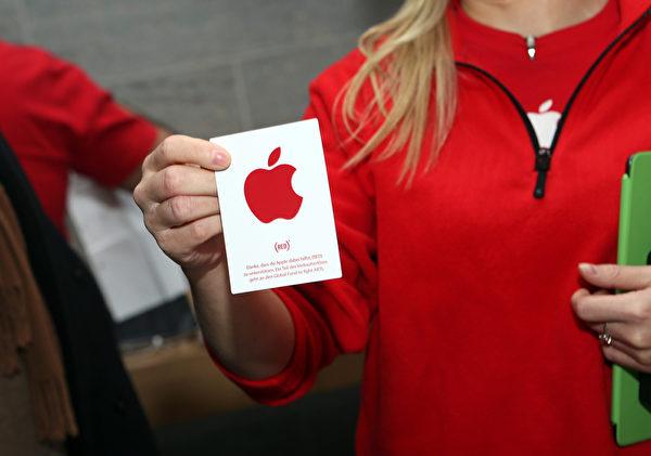 12月1日,在世界爱滋病日,苹果公司一名员工展示了在Apple Store上(RED)标志的贴纸。苹果公司将捐赠一部分收益给全球基金抗击疾病。(Adam Berry/Getty Images for Apple)