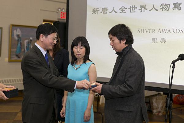 中国画家李奔以画作《撼不动的正信》获得银奖,图为新唐人电视台副总裁(左)为李奔(右)颁奖。(戴兵/大纪元)