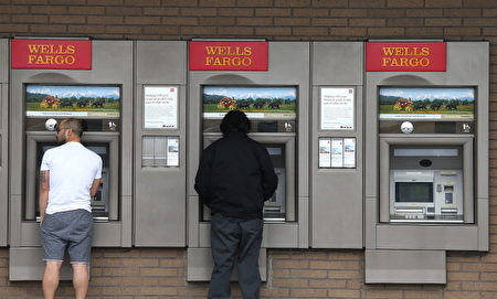 图为客户在富国银行外使用ATM机。(Justin Sullivan/Getty Images)