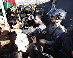 巴勒斯坦自治區閣員艾因(白衣者),於2014年12月10日與遊行示威人士進入以色列屯墾區遊行,遭維安的以色列邊防軍警掐頸致死。(ABBAS MOMANI/AFP/Getty Images)