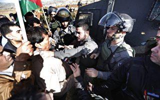巴勒斯坦自治区阁员艾因(白衣者),于2014年12月10日与游行示威人士进入以色列屯垦区游行,遭维安的以色列边防军警掐颈致死。(ABBAS MOMANI/AFP/Getty Images)