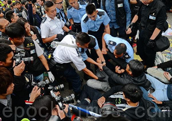 11日下午金鐘清場行動,在場大批佔領人士,包括多名泛民立法會議員、學聯及學民思潮成員,手扣手坐在地上,堅持留守,警員將他們拘捕帶返警署。(宋祥龍/大紀元)