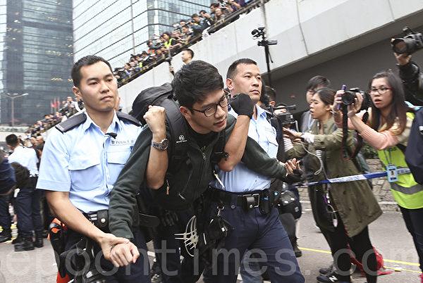 下午金鐘清場行動,在場大批佔領人士,包括多名泛民立法會議員、學聯及學民思潮成員,手扣手坐在地上,堅持留守,警員將他們拘捕帶返警署。圖為學聯常委鍾耀華。(余鋼/大紀元)