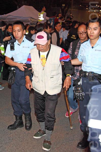 2014年12月11日,在禁制令清場後,香港警方出動大批警力對金鐘雨傘廣場進行全面的清場,並拘捕多名泛民主派立法會議員和學生代表,九旬的黃老伯是年級最大的被捕者。(潘在殊/大紀元)