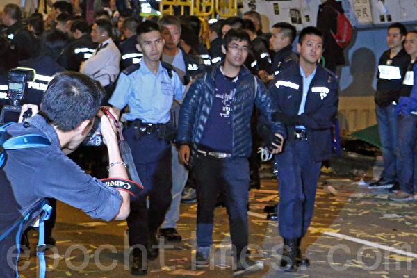 2014年12月11日,在禁制令清場後,香港警方出動大批警力對金鐘雨傘廣場進行全面的清場,學聯秘書長周永康是最後被捕的一批人士。(蔡雯文/大紀元)