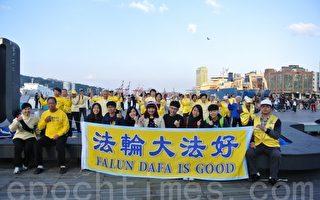法轮功学员海洋广场弘法炼功,现场一片祥和美好,游客争相拍照留念。(周美晴/大纪元)