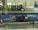 英国航管中心电脑12日当机导致班机停飞和1万名乘客误点。图为伦敦盖威克机场北航站休息室一名旅客。(JUSTIN TALLIS/AFP/Getty Images)