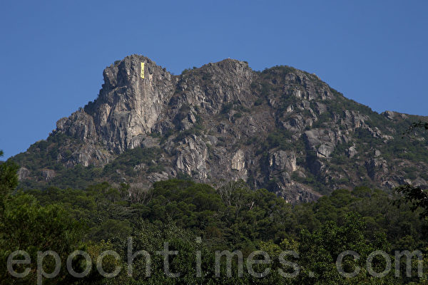 2014年12月13日,雨傘運動剛剛落幕兩天,作為香港地標之一的獅子山再次掛上大型橫幅,內容是CY(梁振英)下台。(潘在殊/大紀元)