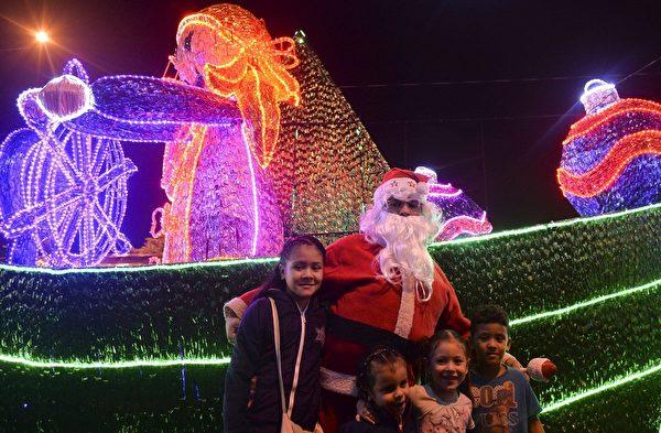 2014年12月9日,哥伦比亚安蒂奥基亚省麦德林,一名男子装扮成圣诞老人带着孩子欣赏圣诞灯饰。(RAUL ARBOLEDA/AFP/Getty Images)