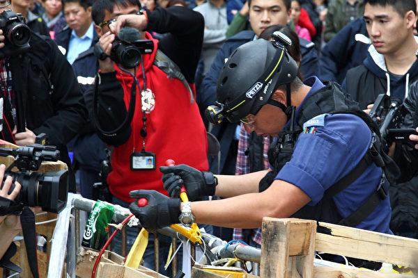 2014年12月15日,銅鑼灣佔領區,警方特別戰術小隊用鐵鉗剪斷索帶,移離鐵馬,出動電鋸鋸開大型木板,清走帳幕雜物。(潘在殊/大紀元)