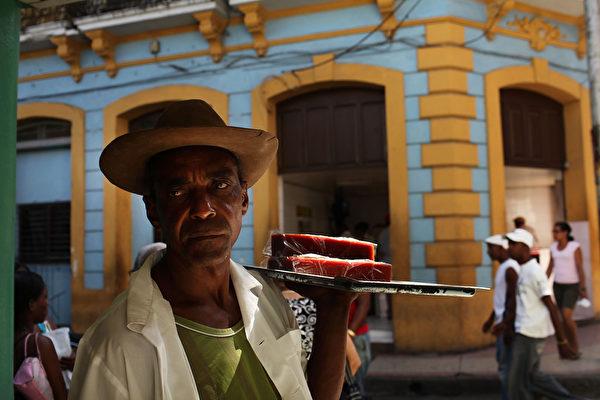 2012年3月24日,古巴第二大城市聖地亞哥街頭,一男子在售賣食物。自1959年施行共產主義制度以來,古巴於2011年首次放寬對私有經濟的限制,以讓大量失業的原國有企業職工自謀生路。(Spencer Platt/Getty Images)