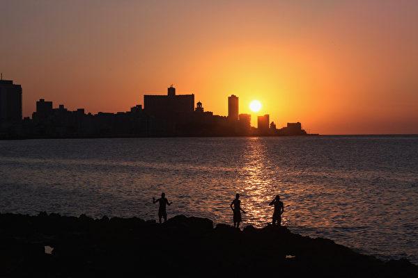 2012年3月24日,夕陽西下的哈瓦那海岸,幾個年輕人在釣魚。(Joe Raedle/Getty Images)