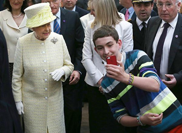 6月24日,英国女王伊丽莎白二世出访北爱尔兰的贝尔法斯特时,被一男青年自拍。(PETER MACDIARMID/AFP)