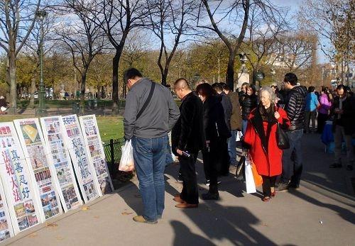 中国游客在巴黎景点观看展板,了解真相。(明慧网)