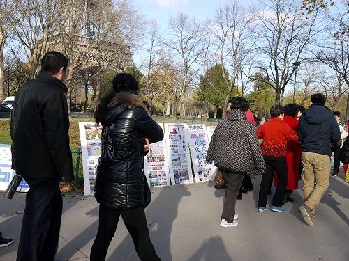 成群结队的中国游客路过巴黎铁塔下的法轮功真相点。(明慧网)