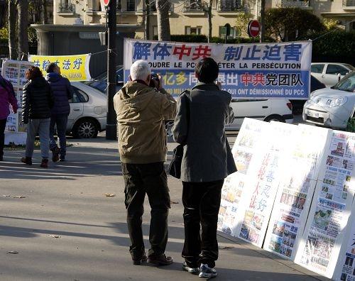 中国游客在巴黎景点埃菲尔铁塔下拍摄法轮功学员制作的真相横幅。(明慧网)