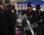 周二(12月23日)又一非裔青年在密苏里州的伯克利被枪杀后,抗议人群连续两天上街抗议。图为枪击案现场维安警察。(Michael B. Thomas/AFP/Getty Images)