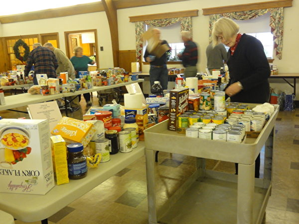「愛心疏困」項目成員正在忙碌的為本社區30多戶貧困民眾準備聖誕期節食物和日常基本生活的必需品。(高聆/大紀元)