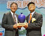 图:陈荣昌(右)2014年接受台湾国立中山大杰出校友奖。(大纪元资料)