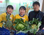 双胞胎的柏羽和柏汶俩人因种菜改变了偏食的习惯,在欢庆丰收时和指导老师徐豫华合影。(黄淑贞/大纪元)