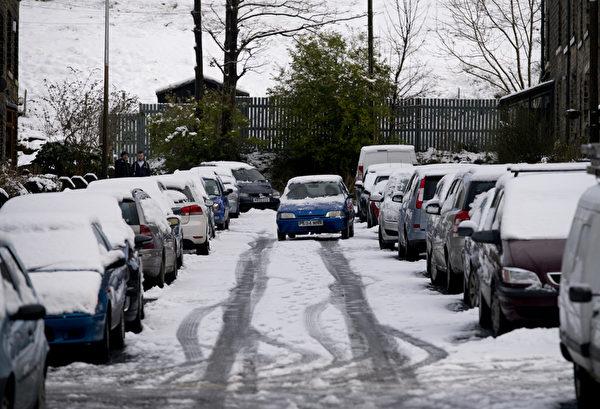 2014年12月27日,英格兰北部马斯登村附近,车子被雪覆盖。(OLI SCARFF/AFP)