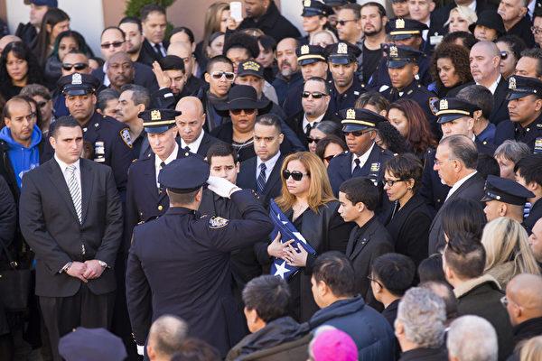 2万5千警察给纽约殉职警察拉莫斯送葬,警察拉莫斯的妻子接过覆盖丈夫灵柩的美国国旗。(戴兵/大纪元)