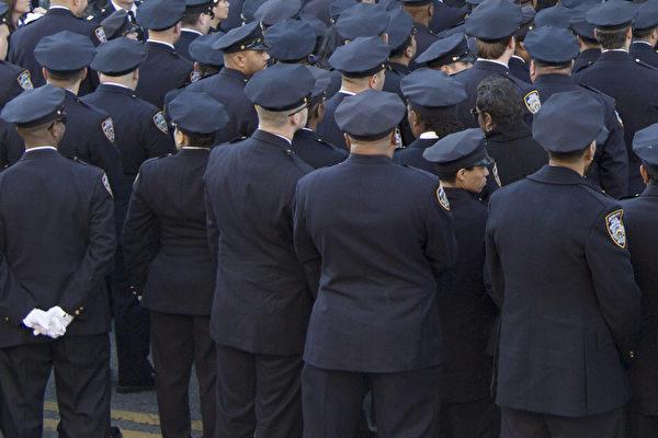 在纽约市长白思豪在殉职警察拉莫斯的葬礼上发言时,聚集在教堂外的纽约警员集体背过身去,表达对市长前段时间默许反警示威的不满。(戴兵/大纪元)