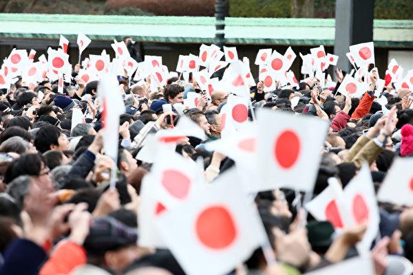 2015年1月2日,日本東京,日皇明仁今天率領皇室成員,在皇宮陽台上舉行新年一般參賀。圖為參拜民眾揮揮舞著日本國旗。(Ken Ishii/Getty Images)