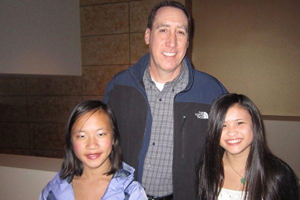 電信公司的會計經理Scott Grunwald帶兩位領養自中國的可愛女兒Bailey和Zoe來看神韻。(漢民/大紀元)