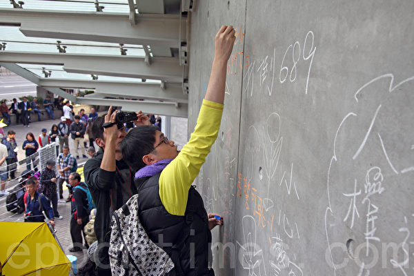 """多个团体在政总外的""""连侬墙""""下声援被捕的涂鸦少女,有市民效仿少女在墙上用粉笔涂鸦。(潘在殊/大纪元)"""