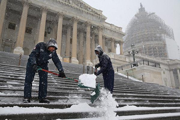 1月6日,在華盛頓特區,工人正在清除國會大廈前階梯的積雪。(Chip Somodevilla/Getty Images)