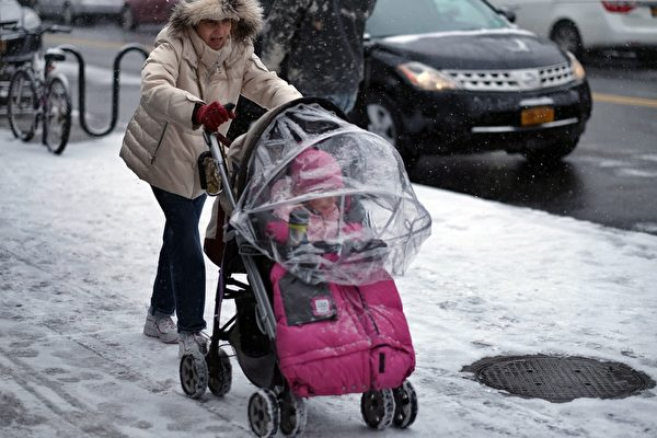 1月6日,在紐約皇后區的風雪中,一個女性推著嬰兒車帶寶寶出門。(Photo credit should read JEWEL SAMAD/AFP/Getty Images)