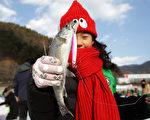 2015年1月10日,韩国华川郡举办华川山川鱼节。图为游客展示鱼获。(Chung Sung-Jun/Getty Images)