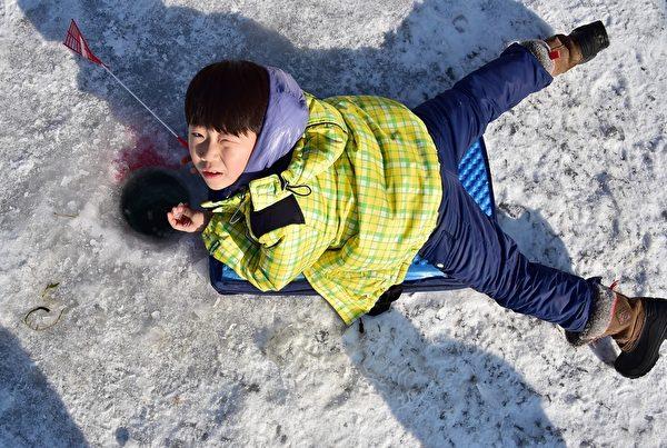 2015年1月10日,韩国华川郡举办华川山川鱼节。图为小孩在冰上钓鱼。(JUNG YEON-JE/AFP)