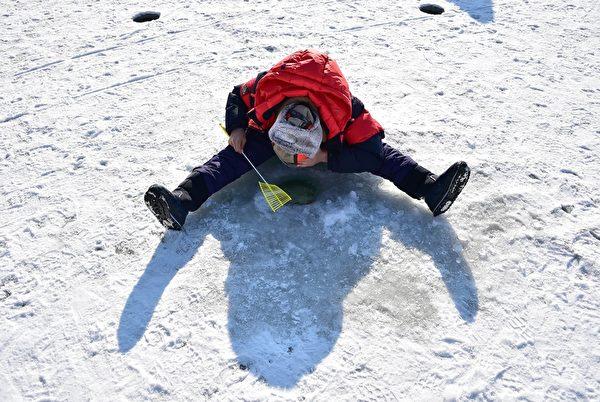 2015年1月10日,韩国华川郡举办华川山川鱼节,游客享受在冰上钓鱼的乐趣。(JUNG YEON-JE/AFP)