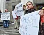 """2014年5月,克里米亚和乌东难民于乌克兰议会前手持""""普京住手!"""",""""我要住在我的房子里!""""等标语牌,根据联合国难民署统计,2014年该地区至少有1万人被驱离家园,克里米亚鞑靼人受灾最为严重。 (SERGEI SUPINSKY/AFP)"""