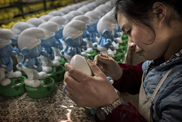图为2014年12月7日福建省德化县一家陶瓷工厂工人在给未完成的陶瓷蓝精灵上色。(Photo by Kevin Frayer/Getty Images)