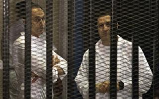 埃及前总统穆巴拉克的两个儿子阿拉(右)和加玛尔(左)26日获释等候贪污案重审。图为两人2013年12月因贪污案出庭。(KHALED DESOUKI/AFP)