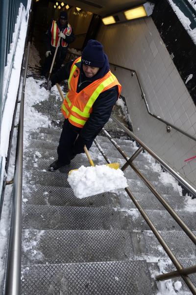 2015年1月27日,紐約法拉盛,清潔人員正在清理地鐵站樓梯上的積雪。(陳正洪/大紀元)