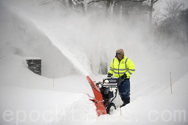 2015年1月波士頓暴風雪,市民手推鏟雪機清雪。(徐明/大紀元)