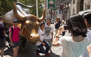 中国境外游人次破亿;在纽约,中国游客已成第四大团体,且颇具消费力。图为2014年7月纽约华尔街的中国游客和夏令营的学生。(戴兵/大纪元)