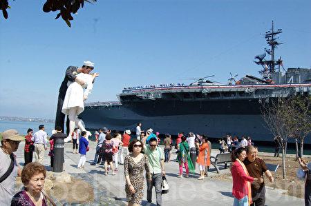 越来越多的中国游客到美国旅游。图为2014年7月在南加州圣地亚哥海港中途岛号航空母舰博物馆景点前的中国游客。(杨婕/大纪元)