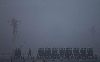 近日大陸媒體突提官員財產公示,大陸學者對此背後中南海的政治局勢進行解讀。圖為天安門廣場嚴重陰霾中的護旗兵。(Photo by Feng Li/Getty Images)