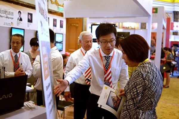 中国富人移民首选国是美国。图为2014年5月17日,北京国际房地产展览会,一位中国妇女向一位美国房地产投资公司的代理人咨询。(WANG ZHAO/AFP/Getty Images)
