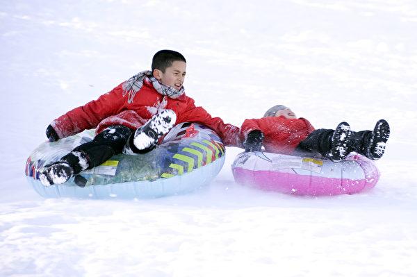 兄弟手牽手共享玩雪的樂趣。(攝影:徐明/大紀元)