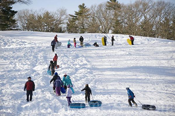 2015波士頓大風暴後,兒童們在斜坡上自上而下滑行玩耍。(攝影:徐明/大紀元)